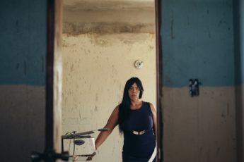 """A Karina Torres la Agencia Federal para el Manejo de Emergencia (FEMA, en inglés) le dijo que las pérdidas en su casa por la inundación no eran suficientemente graves. Angeline """"Beba"""" Marrero no cualificó para un cheque de ayuda inmediata de FEMA y tuvo que esperar hasta ocho meses para que le pusieran un toldo al techo de su residencia. Nunca le dijeron por qué. A Ivana Fred Millán le devolvieron su solicitud en varias ocasiones y la asistencia se tardó siete meses en llegar. Elliot Cruz Morales, sencillamente, no acudió a buscar ayuda por no confrontar prejuicios. """"No fui directamente por el mismo miedo, porque yo dije: 'diantre, esto va a ser un proceso, me van a estar preguntando por qué yo me llamo así, si me veo así'"""", recuerda Elliot, quien perdió todas sus pertenencias luego de que la casa en la que vivía en Vega Baja fuera destrozada por el huracán María en 2017"""
